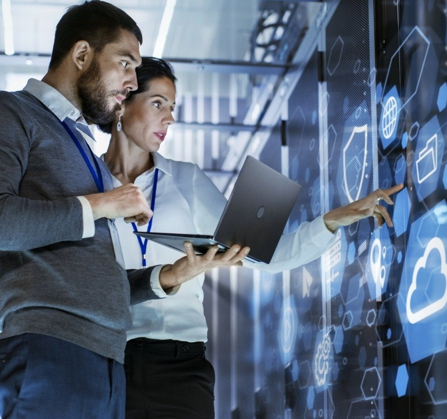 Man and woman reviewing server room's digital display