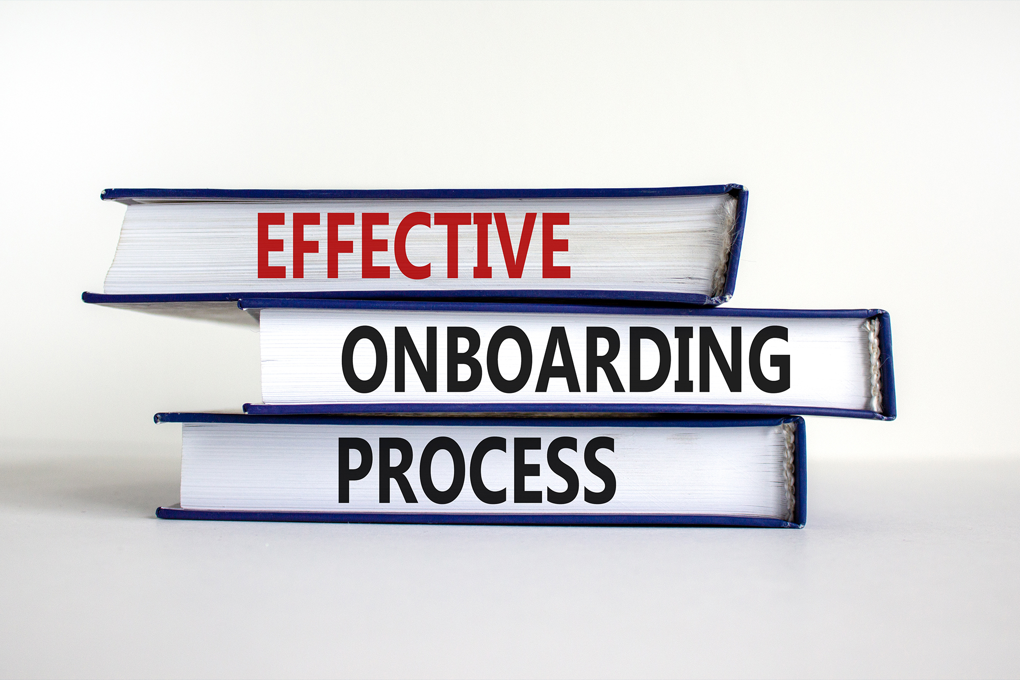 Books stacked with text - Effective, Onboarding, Process